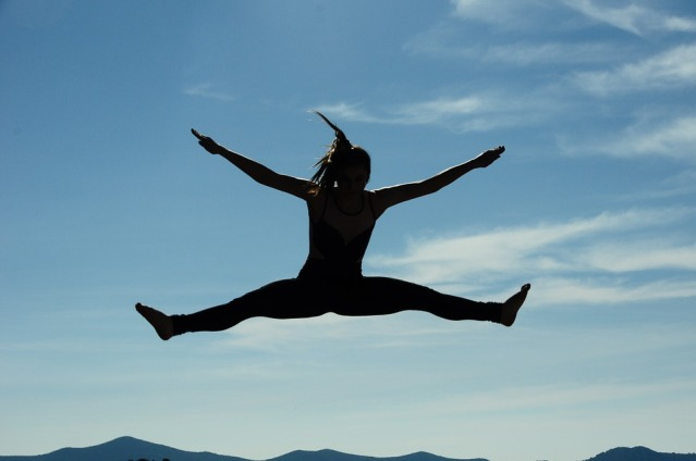 Silhouette of a woman joyfully leaping, widespread arms and legs