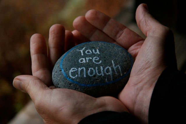 "hands holding a rock that says ""you are enough"""