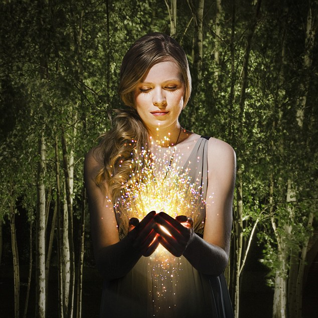 woman in the forest looking at sparklers in her hands
