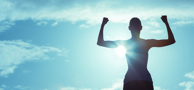 woman showing strength with biceps, bright blue sky and clouds behind her.