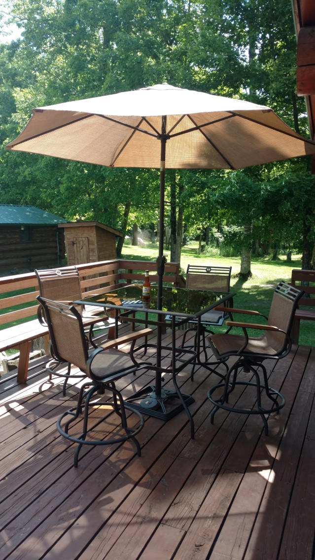 author's deck, with patio furniture, umbrella, and a book and a beer.
