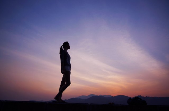 woman silhouette standing at sunset