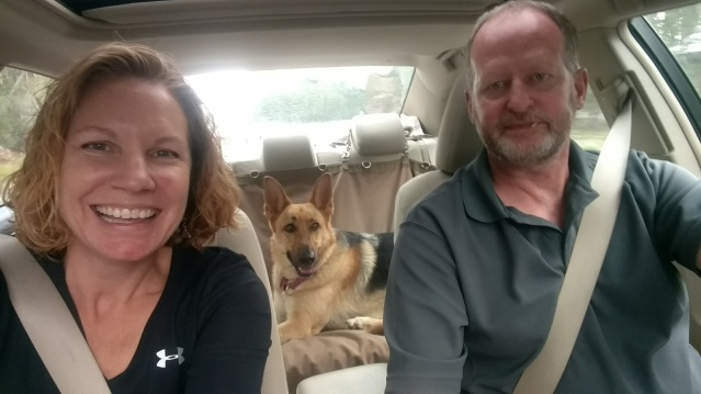 Selfie of the author and her husband in the car, with their German Shepherd in the backseat.