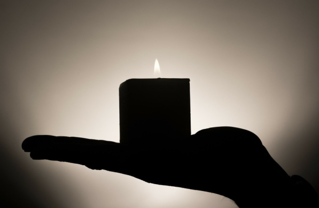 Silhouette of a flat palm holding a lit column candle.