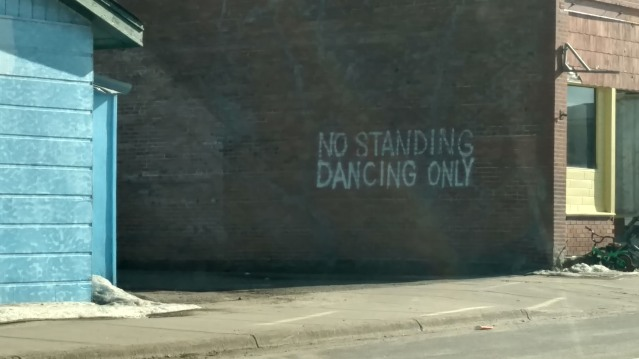 Painted on the alley side of a brick building: No standing dancing only.