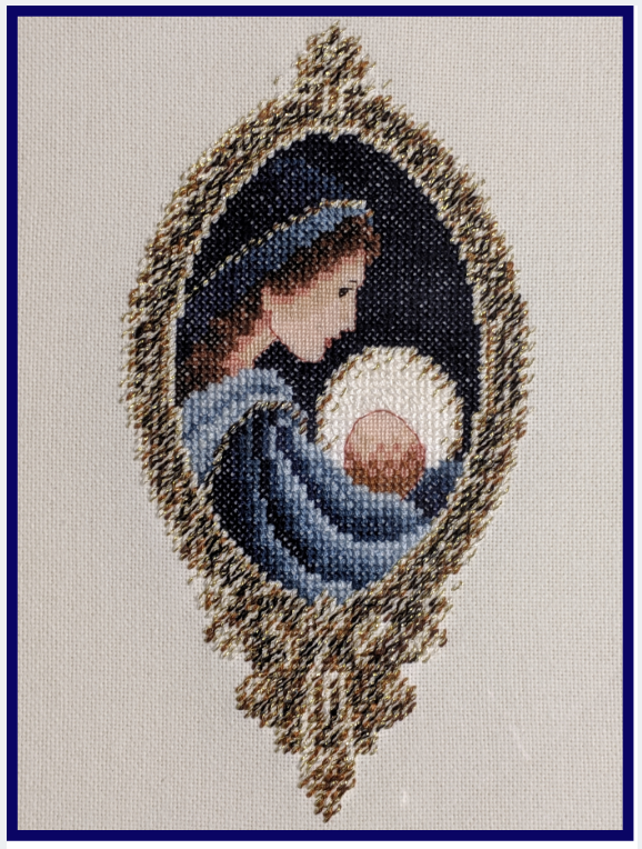 A cross-stitch of the Holy Mother holding the Divine Child that the author