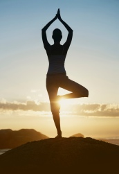 Silhouette of a woman in standing yoga pose at sunset