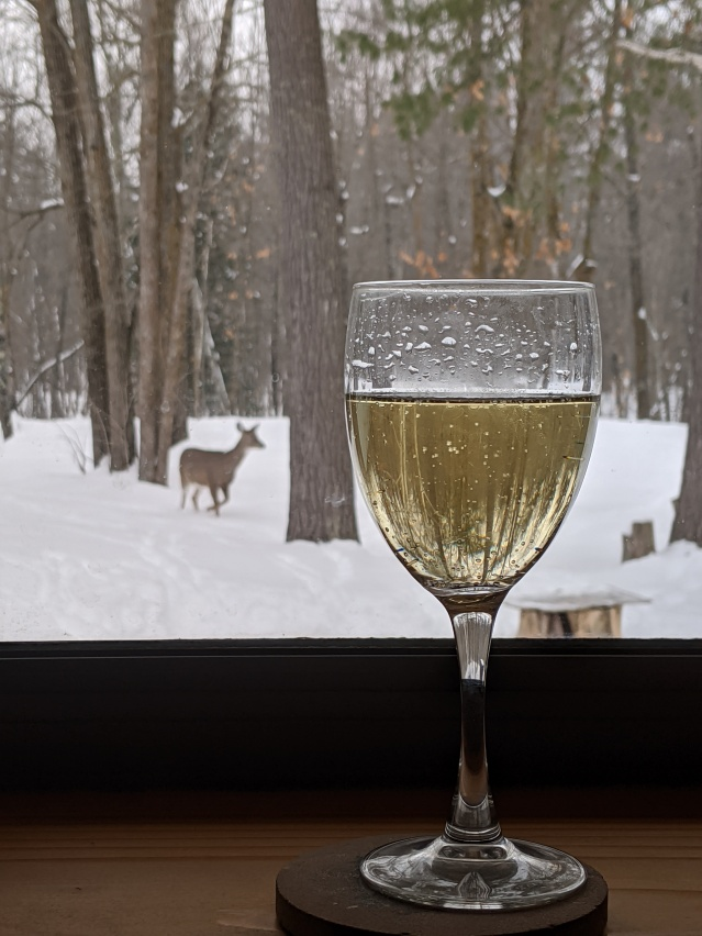 Full wineglass in the foreground focus, snowy woods in the background out the window. A deer in the midground is walking closer.