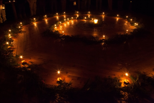 candles and evergreen boughs making a winter spiral on a wood floor.