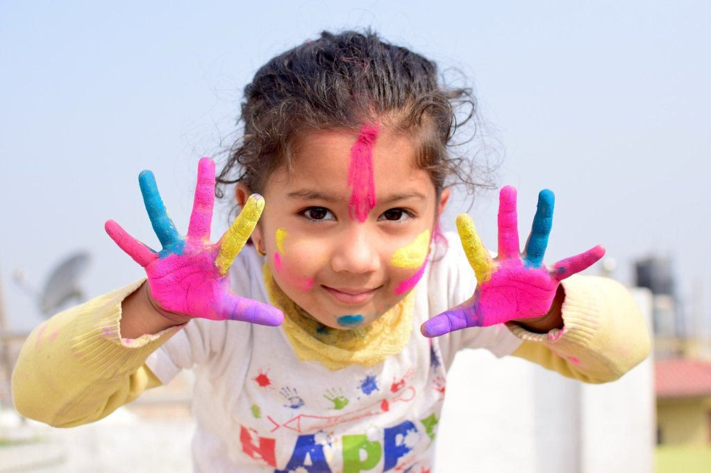 young girl child with hands and face painted bright colors