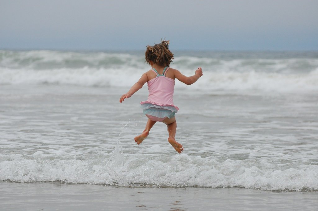toddler jumping into the ocean waves