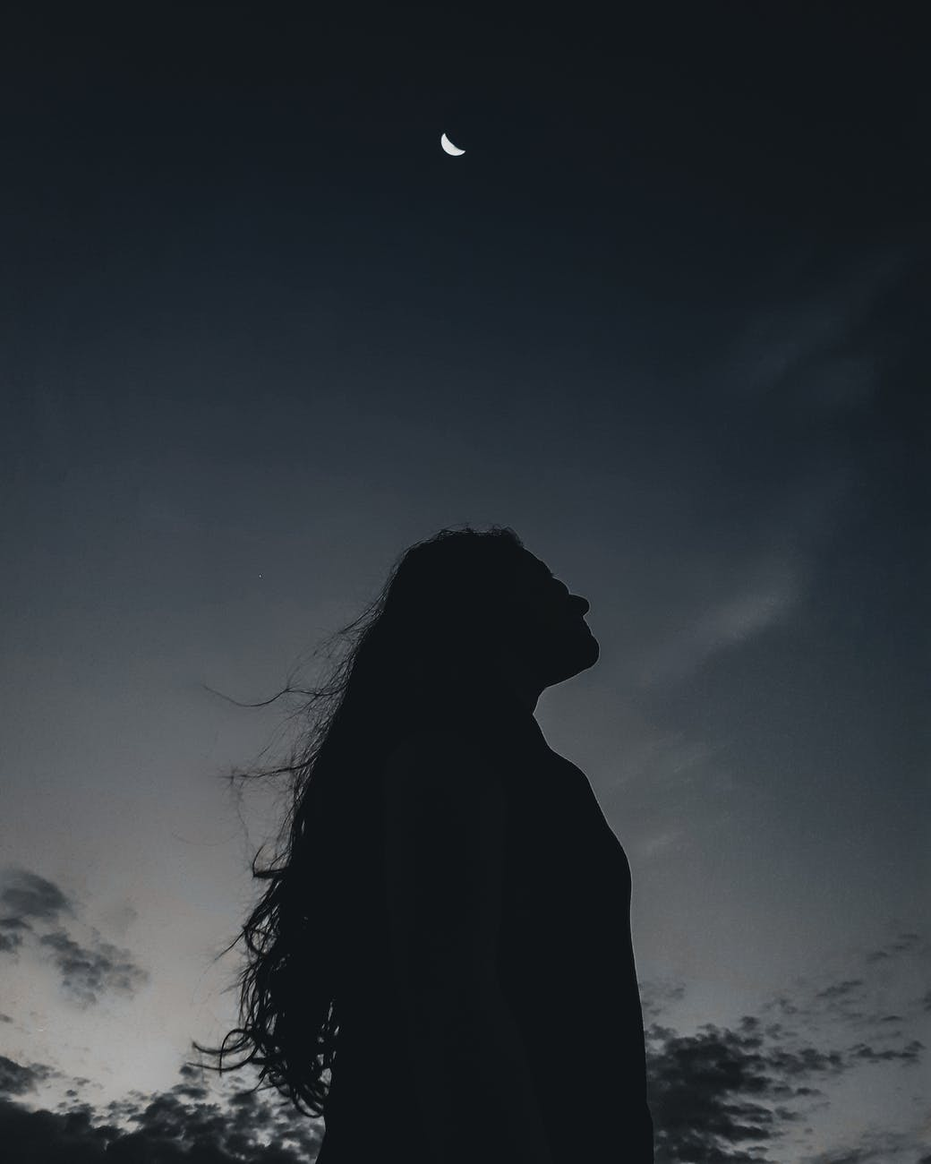 woman under the moonlit sky at twilight